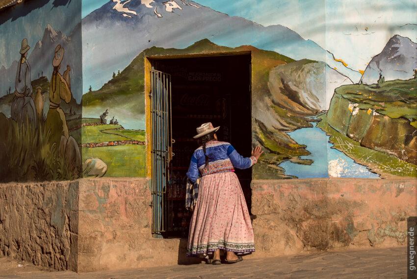 Alte Frau in traditioneller Kleidung vor einheimischem Laden