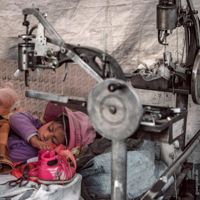Mädchen schläft in der Näh-Werkstatt des Vaters.